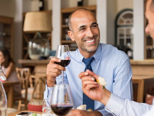 Man with neck tie drinking wine