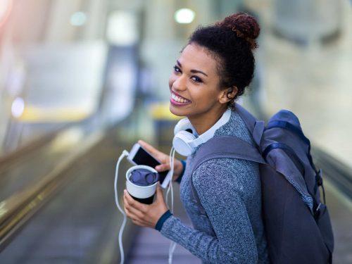 Woman on an escalator drinking coffee